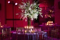 Wedding reception with a tall centerpiece tion tablof white orchids surrounded by floating candles