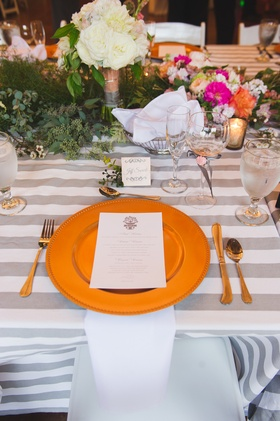 gold charger on gray striped tablecloth with floral runner