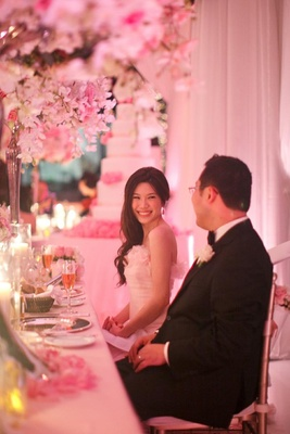 Chinese bride and groom sit at sweetheart table for wedding
