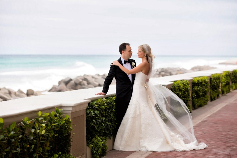 Bride in strapless Vera Wang wedding dress and veil with groom in tuxedo looking over beach