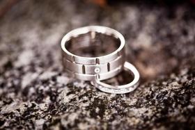 Groom and bride wedding rings with diamonds on rock