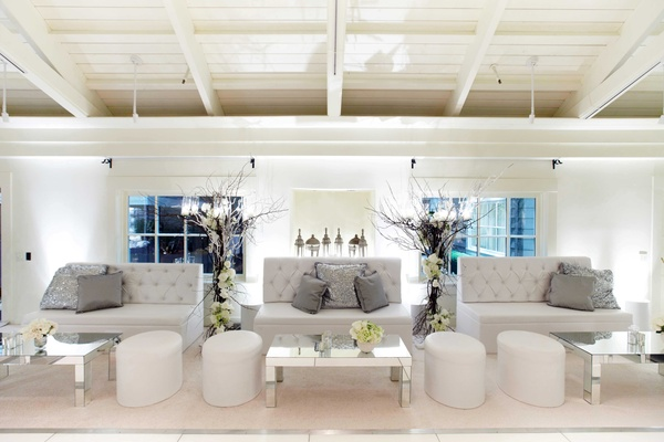 Winter wedding lounge area with white tufted furniture, silver sequin pillows, and mirror tables