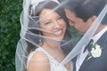 bride and groom smiling with veil draped over their faces