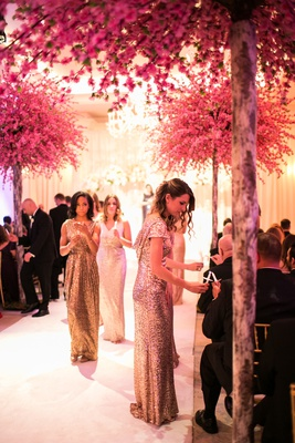 bridesmaids in gold sequin gowns pass out candles to guests for ceremony