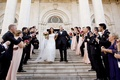 After ceremony bride and groom walk down steps with bubbles blowing from guests