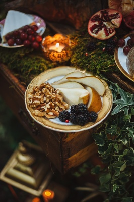 Outdoor wedding with pears, blackberries, and walnut appetizers on a gold rimmed china plate