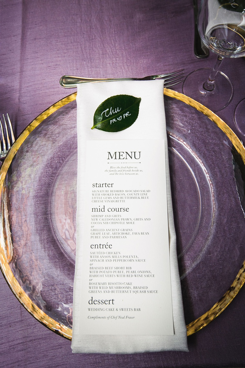 wedding menu on top of linen napkin clear gold charger green leaf place card purple linens