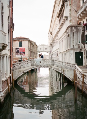 Bride and groom on bridge in venice italy canals historic buildings floating city destination
