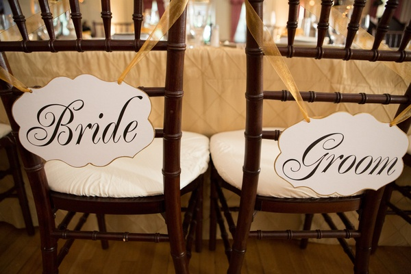 Die-cut signs tied to reception chairs with gold ribbon