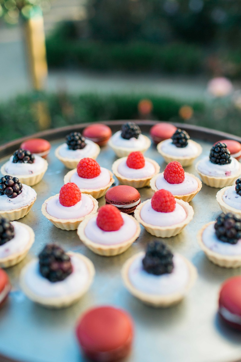raspberry and blackberry tart desserts with red french macaroons on serving tray