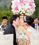 Groom in Vera Wang in Black suit kisses bride in Vera Wang sleeveless gown, jeweled headband