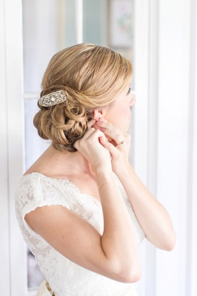 Bride in an Alençon lace Watters gown with cap sleeves, updo, and hair clip with rhinestones