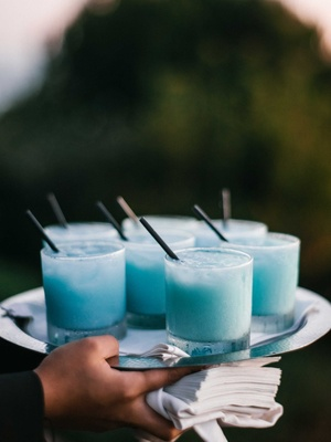 Rocks glass filled with light blue frozen cocktail on silver tray held by server black straws