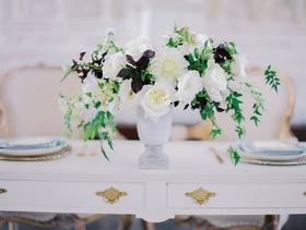 Sweetheart table with white flowers, greenery, purple leaves in an urn at Vibiana