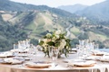 Vineyard wedding winery views of mountains low centerpiece gold plates linens