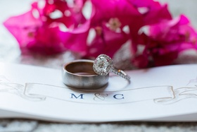 Groom's brushed metal band and bride's diamond engagement ring with round center stone, halo
