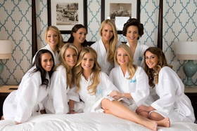 Bride and bridesmaids on hotel bed with white robe and blue monogram gifts