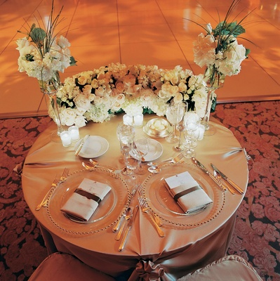 Gold linen wedding couple's reception table with white roses