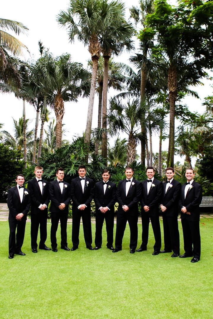 groomsmen pose waring matching black tuxedos