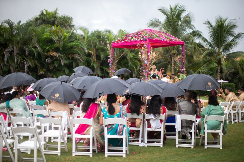 guests holding black umbrellas during outdoor wedding ceremony in the rain