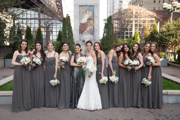 a bride in a white lace wedding gown stands with her bridesmaids clad in gray gowns white bouquets