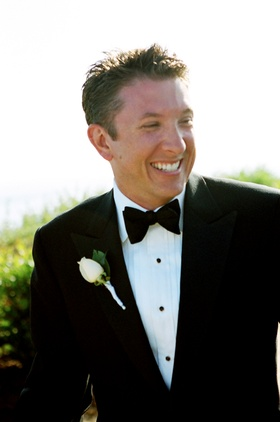Groomsman wearing tuxedo with bow tie and rose