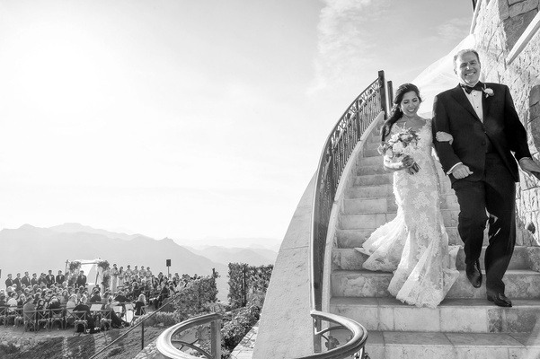 black and white photo of bride in Monique Lhuillier wedding dress walking down stairs with father