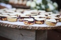 Ranch wedding dessert table with berry tarts topped with hearts on tree trunk slab