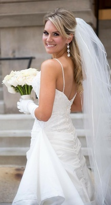 Bride in gloves, veil, dangle earrings, and a spaghetti strap gown with an embroidered bodice