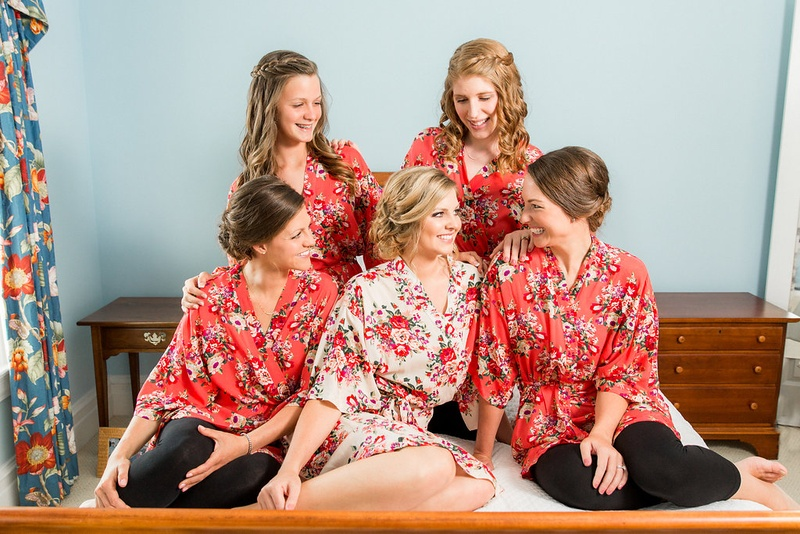 Bride in white pink red wedding robe with bridesmaids in red pink flower print robes on bed bridal