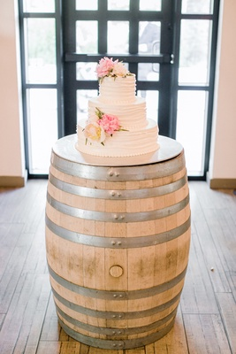White wedding cake with ivory and pink peonies on a wood barrel