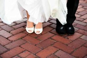 Bride in peep-toe pumps and groom in monogram shoes