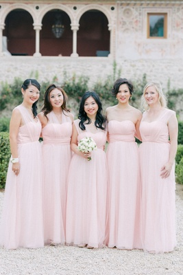 Bridesmaids in light pink long dresses illusion necklines maid of honor holding bouquet