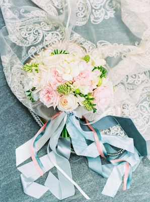 bouquet of pink cream white flowers greenery on lace fabic with pink blue fabric streamers