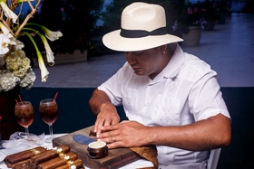 Man in white shirt with cuban hat rolling tobacco leaves for cigar station at wedding