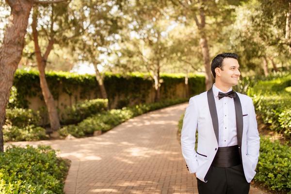 groom in formal tuxedo with cummerbund and white jacket