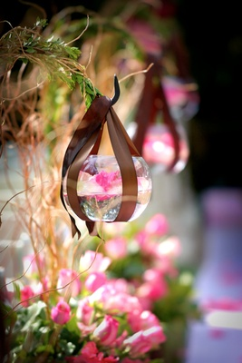 pink orchid floats in glass bowl hung from hook with brown ribbon