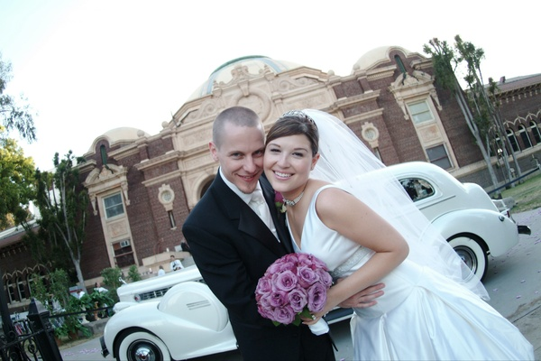Couple in front of classic wedding car and museum