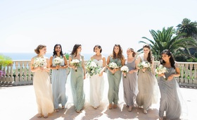 bride and seven bridesmaids in mismatched dresses in soft muted colors of cream, gray, sage, blue
