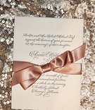 Cream wedding invitation with script font and copper bow
