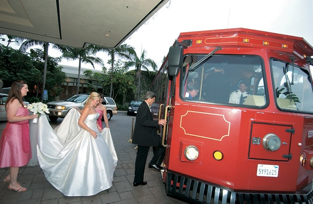 Maid of honor helps bride into transportation