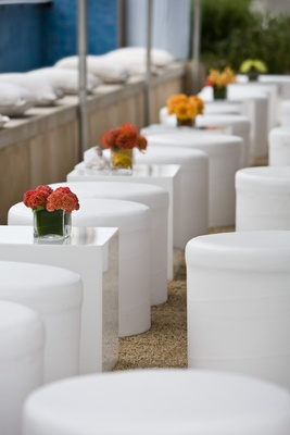 White square tables and round stools and orange flowers