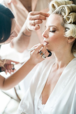 blonde bride with hair in curlers while getting her makeup done