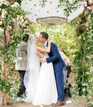 Bride in Maradee Wahl veil and groom in navy blue tie kiss under pretty garden chuppah outside pink