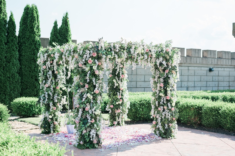 four post ceremony arbor chuppah with greenery, wisteria, hydrangeas