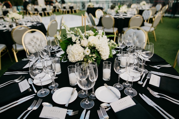 wedding reception table, black linens, grey and gold chairs, small centerpieces with hydrangeas
