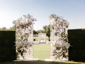 Outdoor ceremony on golf course hedge boxwood wall with white gate greenery white flowers