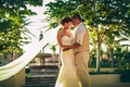 a bride and groom in full wedding attire embrace one another in their outdoor wedding space