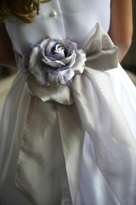 Purple and silver fabric flower on back of flower girl dress