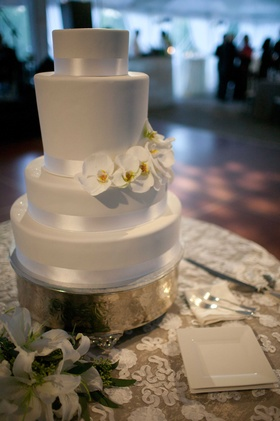 white wedding cake with fresh white flowers on gold plate and white lace table linens